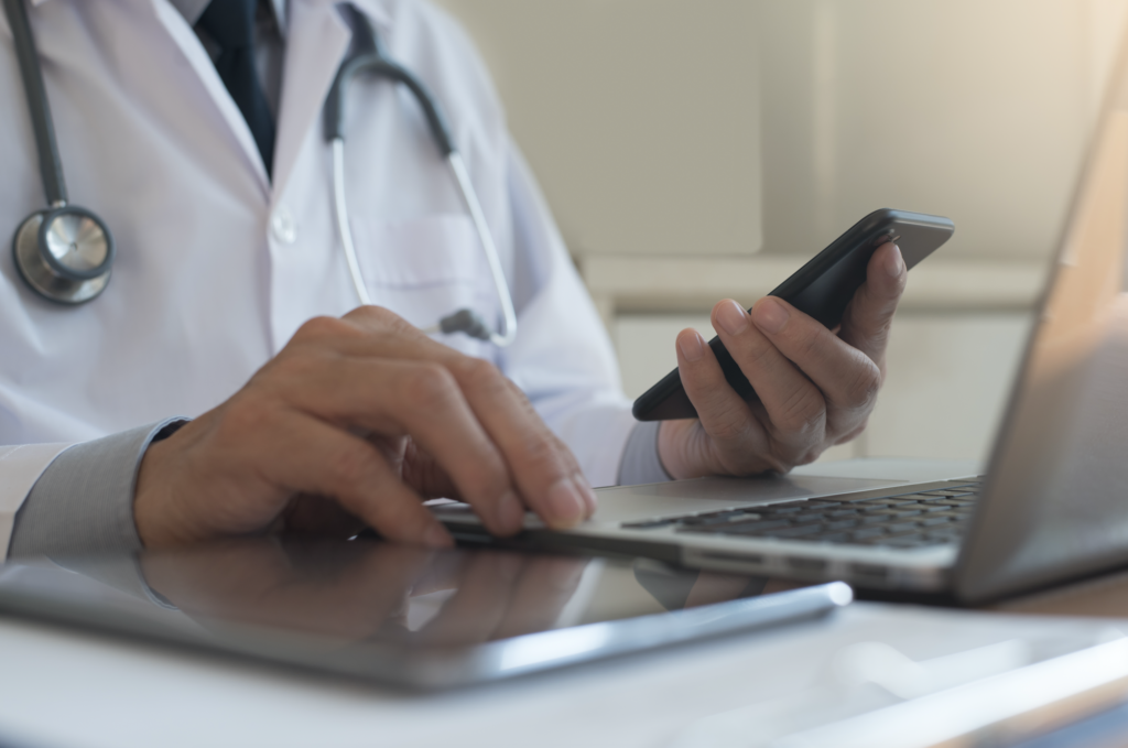 Clinician with mobile phone and computer
